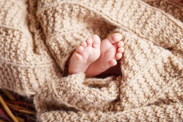 Photo gros plan des pieds de bébé nouveau-né sur plaid tricoté beige. beau concept de l'enfance et de la maternité