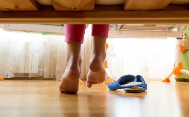 Photo gros plan de pieds féminins sous le lit
