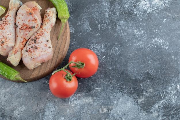 La photo en gros plan de pilons de poulet épicé cru avec du poivron vert et des tomates.