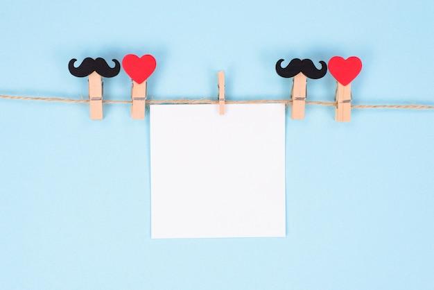 La photo en gros plan de pinces à linge suspendu à une corde avec une feuille de papier vierge fond de couleur pastel isolé