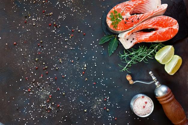 Photo de gros plan de poisson de saumon frais avec des tranches de sel de mer et de lime sur tableau noir