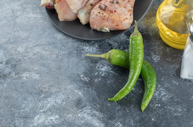 La photo en gros plan de poivrons frais avec des cuisses de poulet et de l'huile.