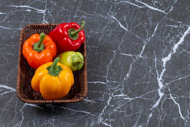 La photo en gros plan de poivrons mûrs frais dans un panier tressé