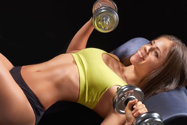Photo gros plan d'un portrait de femme de sport portant des vêtements de sport noir avec des haltères de pompage des muscles biceps sur dark
