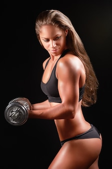 Photo gros plan d'un portrait de femme sportive portant des vêtements de sport noir sur haltère de levage sombre