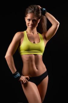 Photo gros plan d'un portrait de femme sportive portant des vêtements de sport noirs sur dark