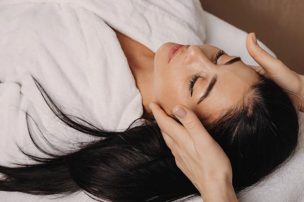La photo en gros plan d'une procédure de massage de la tête effectuée par un travailleur du spa au salon