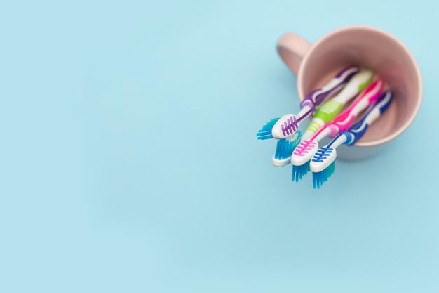 Photo en gros plan de quatre brosses à dents multicolores dans un porte-gobelet sur un fond bleu avec copie espace, vue du dessus