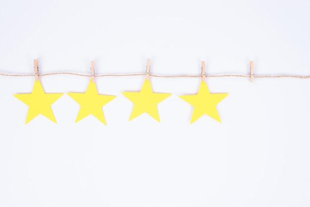 La photo en gros plan de quatre des cinq golden start accroché sur le fil attaché avec peu de pings isolé fond de couleur blanche