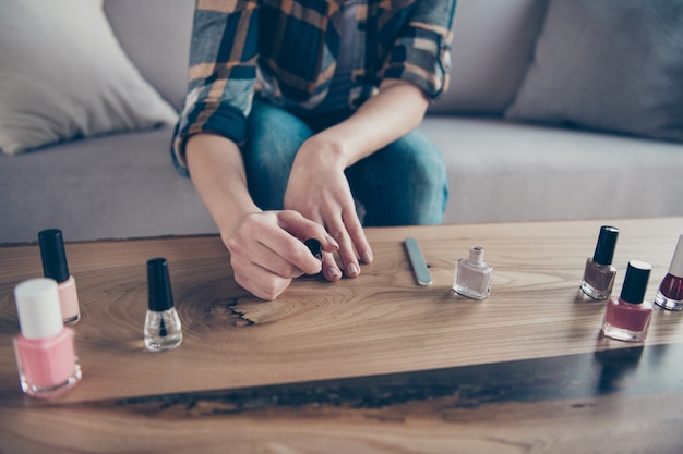 Photo gros plan recadrée de dame a fait correction des ongles en appliquant la couche de finition polonaise tenant la main sur la table porter des vêtements décontractés assis confortable canapé appartement à l'intérieur