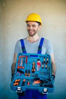 La photo en gros plan d'un réparateur professionnel en uniforme et d'un casque de sécurité tient en main de nouveaux outils modernes pour le travail et la rénovation