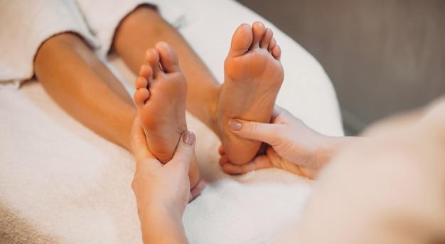 La photo en gros plan d'une séance de massage des pieds à une jeune femme allongée sur le canapé dans un salon spa