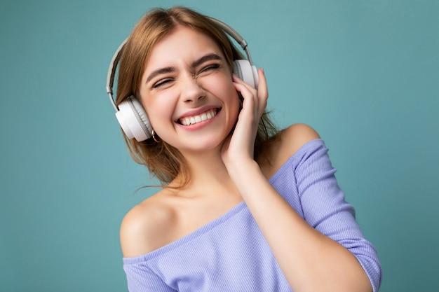 Photo gros plan de sexy assez heureuse souriante jeune femme blonde portant un haut court bleu isolé sur