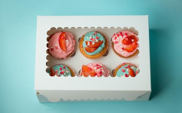 Photo en gros plan de six cupcakes colorés décorés de pépites et de fraises dans une boîte en papier fermée