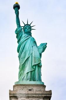 Photo gros plan de la statue de la liberté par une journée ensoleillée et ciel bleu avec des nuages. île de la liberté. nyc, états-unis.