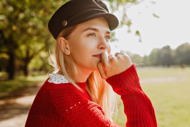 Photo gros plan d'une superbe blonde profitant du soleil dans le parc en automne. beau portrait de jeune femme debout sous les arbres jaunes.