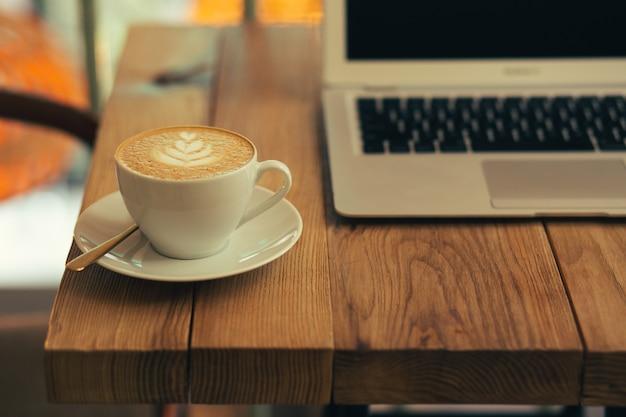 Photo en gros plan d'une surface de table en bois avec un ordinateur portable moderne debout sur l'arrière-plan et une tasse de café au lait au premier plan