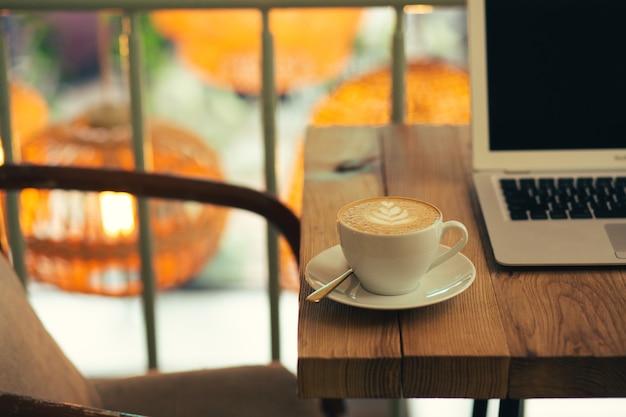 Photo en gros plan d'une table de café confortable avec un ordinateur portable moderne et une tasse de café au lait sur la surface en bois
