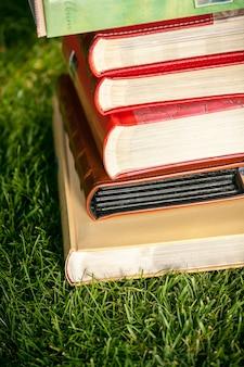 Photo gros plan de tas de livres colorés allongé sur l'herbe à la journée ensoleillée