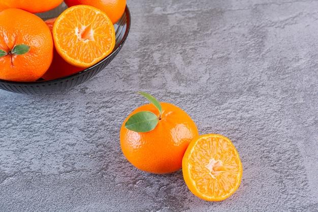 La photo en gros plan de tas de mandarines biologiques sur fond gris.