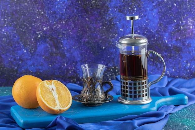 La photo en gros plan de la théière en verre avec du verre et du citron.