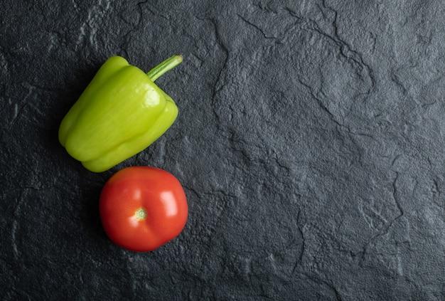 La photo en gros plan de la tomate et du poivre sur fond noir