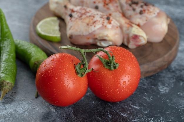 La photo en gros plan de tomates et poivrons biologiques frais avec des cuisses de poulet cru.