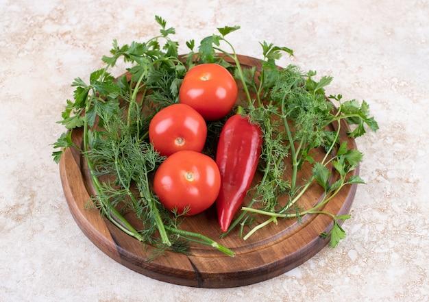 La photo en gros plan de tomates et de poivrons avec des verts sur planche de bois.