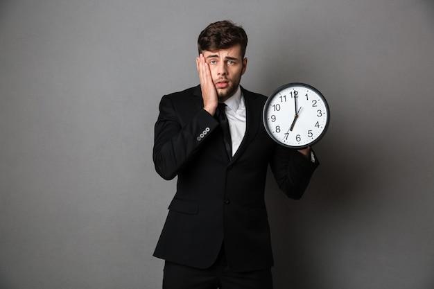 Photo en gros plan d'un travailleur bouleversé en costume tenant une horloge,