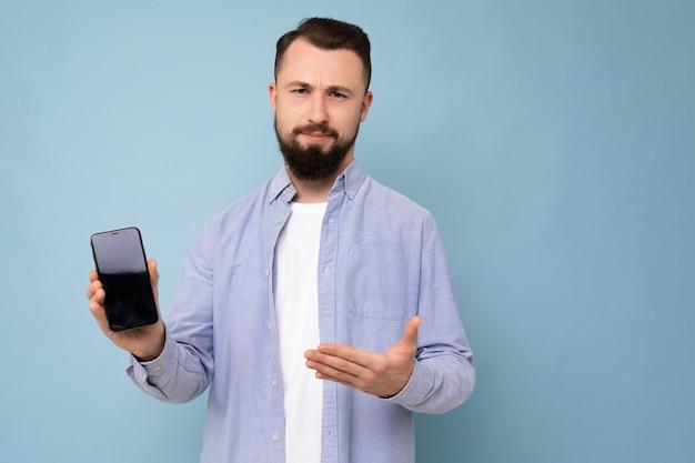 Photo en gros plan de triste insatisfait beau beau jeune homme mal rasé brune avec une barbe portant un t-shirt blanc décontracté et une chemise bleue en équilibre isolé sur fond bleu avec un espace vide tenant