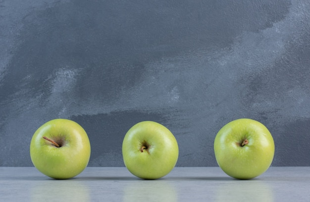 La photo en gros plan de trois pommes fraîches vertes.