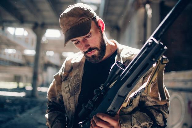 Une photo d'un guerrier debout dans un hangar et regardant son fusil. il le nettoie et le prépare au combat. il y a une belle journée ensoleillée à l'extérieur du hangar.