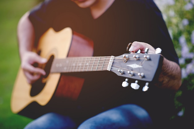 Photo d'un guitariste, un jeune homme jouant de la guitare assis dans un jardin naturel, concept musical