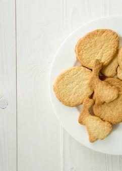Photo d'en haut du plat avec des cookies sur un bureau blanc