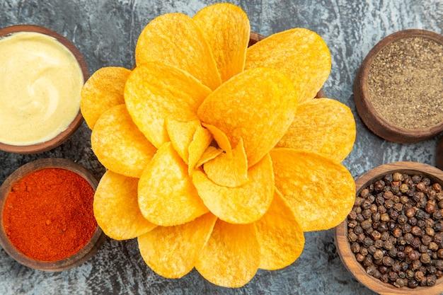 Photo haute résolution de chips maison décorées comme des fleurs en forme de fleur dans un bol brun sur table grise
