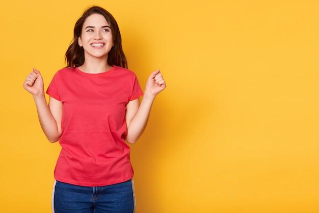 Photo de heureuse belle jeune femme serrant le poing tout en souriant et en levant isolé sur jaune