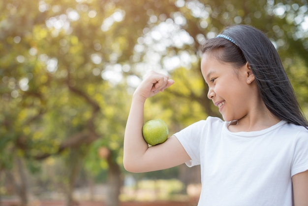 Photo heureuse petite fille asiatique enfant debout avec un grand sourire. fille avec pomme verte montrant les biceps. nature bio verte saine et fraîche avec feuillage flou abstrait et lumière du soleil d'été