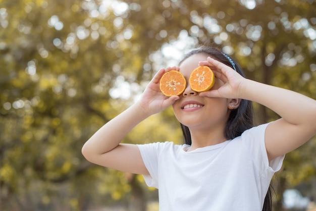 Photo heureuse petite fille asiatique enfant debout montrant les dents de devant avec grand sourire. couvrant les yeux d'orange avec un feuillage flou abstrait et un été lumineux.