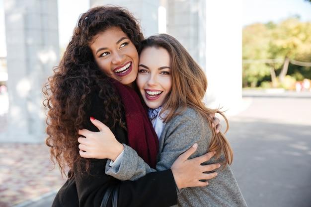 Photo de l'heureuse réunion de deux amis s'embrassant avec la rue en arrière-plan. fille caucasienne regardant la caméra. dame africaine regarde de côté.