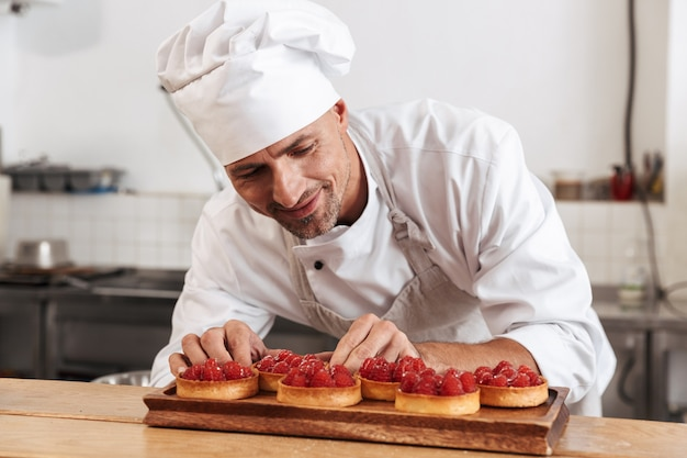 Photo de l'heureux chef masculin en uniforme blanc tenant la plaque avec des gâteaux