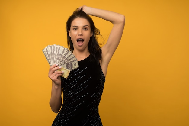 Photo de heureux heureux jeune femme posant isolé sur fond de mur jaune tenant de l'argent et une carte de crédit ou de dette.
