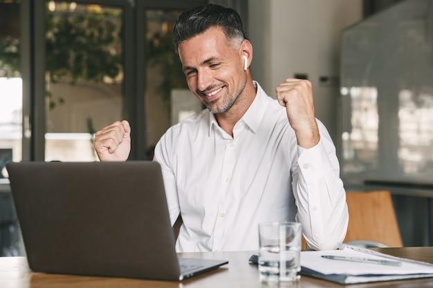 Photo d'heureux homme d'affaires de 30 ans portant une chemise blanche et des écouteurs sans fil se réjouissant et serrant le poing, tout en travaillant sur un ordinateur portable au bureau
