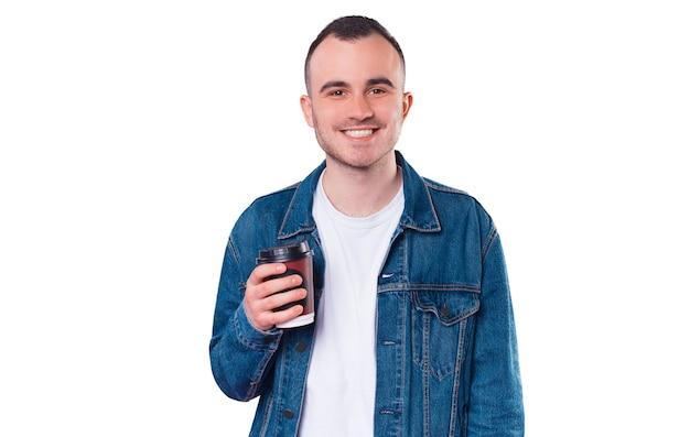 Photo d'heureux jeune bel homme tenant une tasse de café pour aller
