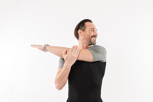Photo d'un heureux sportif de 30 ans portant une montre intelligente et un t-shirt souriant et étirant les bras pendant l'échauffement