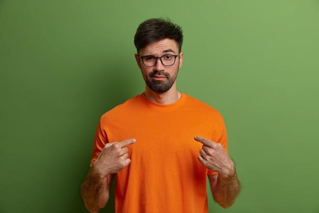 Photo de hipster impertinent et effronté confiant se pointe sur lui-même, dit que vous pouvez compter sur moi, porte des lunettes et un t-shirt orange, isolé sur un mur vert. homme barbu arrogant assertif à l'intérieur