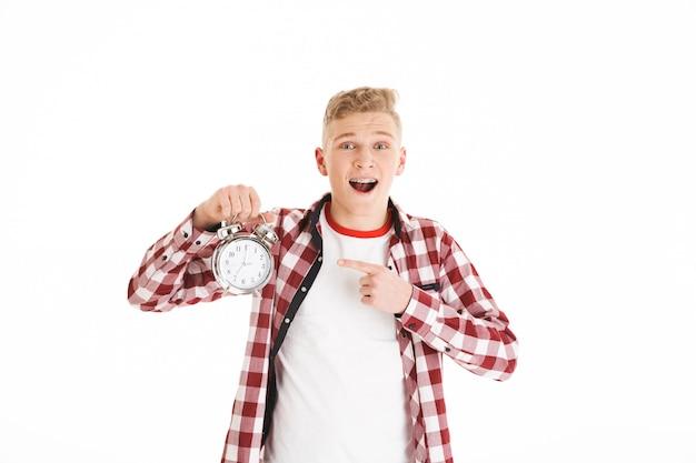 Photo d'un homme adolescent confus portant une chemise à carreaux tenant une alarme et pointant le doigt sur le cadran de l'horloge, isolé sur un mur blanc