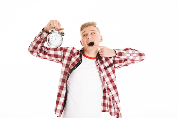Photo d'un homme adolescent heureux portant une chemise à carreaux tenant une alarme et pointant le doigt sur le cadran de l'horloge, isolé sur un mur blanc