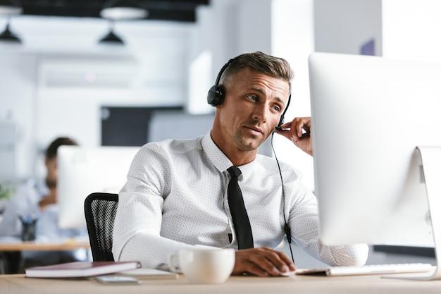 Photo d'un homme adulte de 30 ans portant des vêtements de bureau et des écouteurs, assis par ordinateur dans le centre d'appels