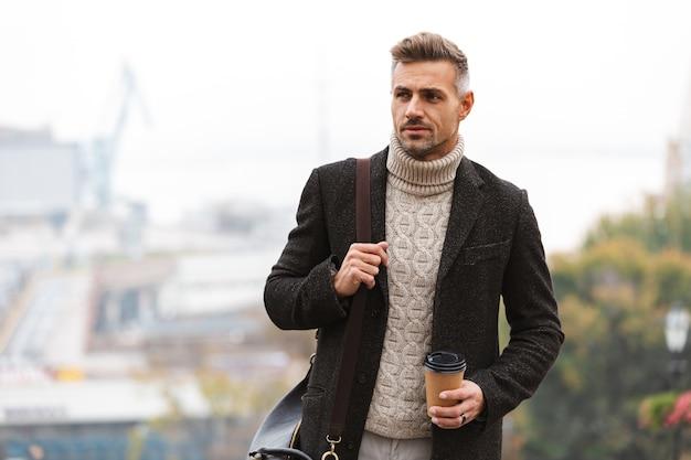 Photo d'un homme adulte européen de 30 ans portant une veste tenant un café à emporter, tout en marchant dans la rue de la ville