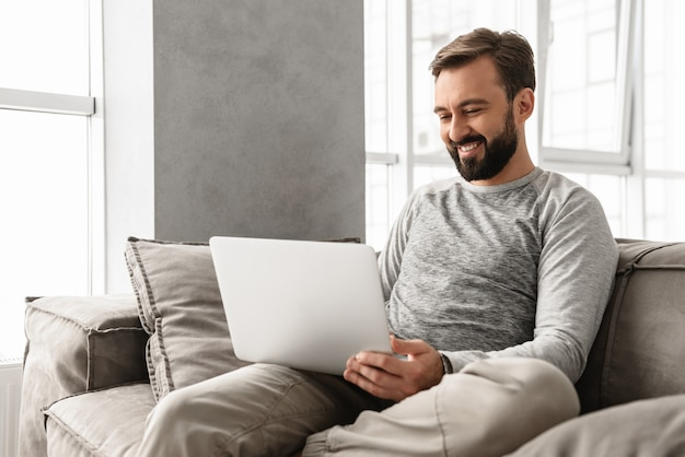 Photo d'un homme adulte heureux de 30 ans en vêtements décontractés en tapant sur un ordinateur portable, tout en travaillant dans une maison confortable